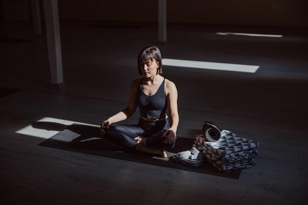 Young calm yogi woman in lotus yoga pose. yoga studio interior.