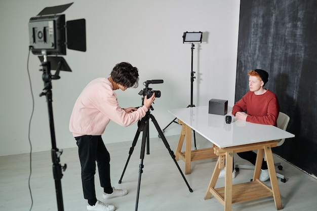 Young cameraman bending in front of video shooting equipment while standing in studio in front of male vlogger
