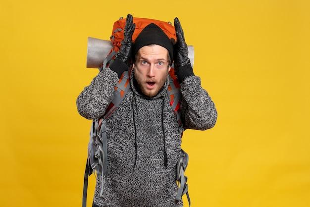 Молодой турист в кожаных перчатках и рюкзаке держит голову