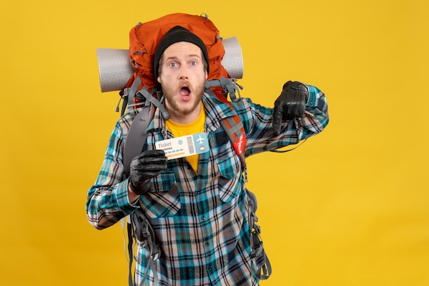 Giovane camper con black hat e zaino in possesso di biglietto aereo rivolto a floor