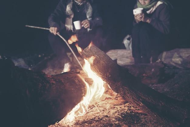 Молодой кемпинг для отдыха. молодой огонь во время кемпинга для тепла