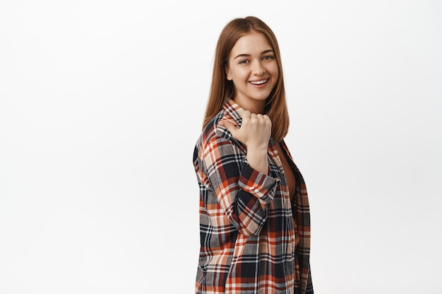 若い率直な女性、彼女の肩の後ろに親指を指して、友好的で自信を持って前に微笑んで、道を示し、場所をお勧めし、白い壁に立っている女性
