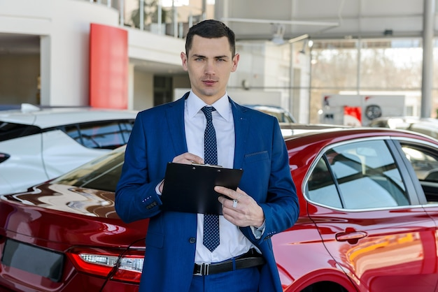Young car dealer holding clipboard in salon