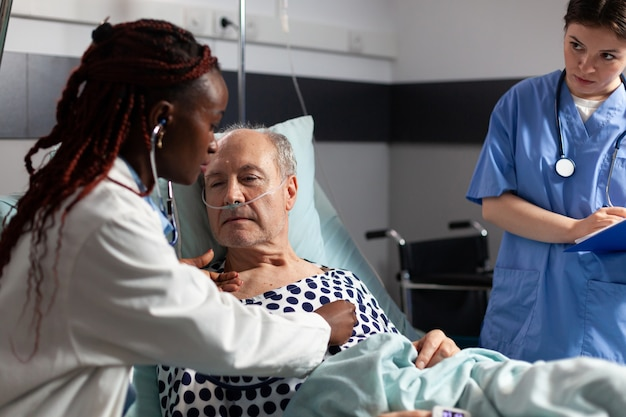 Young cardiologist checking examining senior patient heart, using stethoscope while patient is laying in hospital bed to set diagnosis for therapy, breathing with help from test tube
