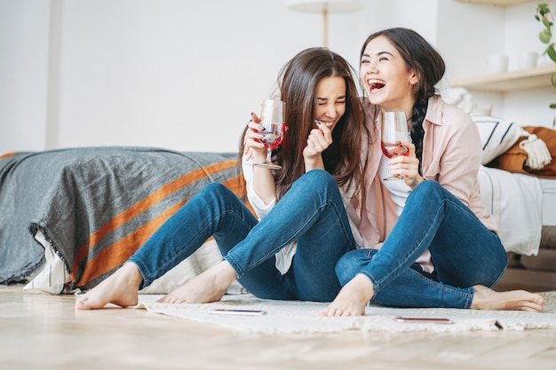 Young carefree laughing brunette girls friends in casual with glasses of wine having fun together on home party