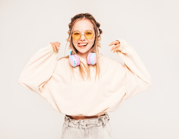 Young carefree model listening to music in wireless headphones