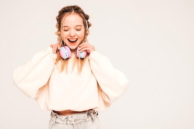 Молодая беззаботная модель слушает музыку в беспроводных наушниках