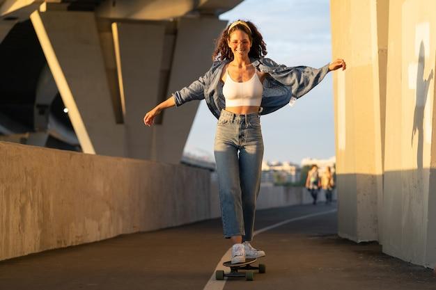 근심 없는 젊은 여성은 트렌디한 거리 스타일의 옷을 입고 일몰 행복한 소녀에서 스케이트보드를 타는 것을 즐깁니다.