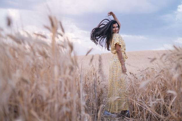 Молодая беззаботная женщина, наслаждаясь природой, позируя в пшеничном поле.