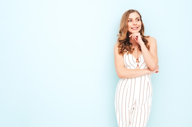 Young carefree woman posing near light blue wall in studio