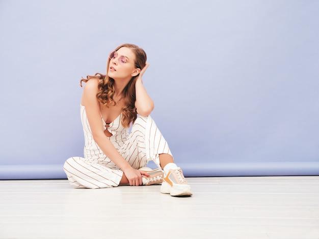 スタジオで紫色の壁の近くでポーズをとってのんきな若い女性