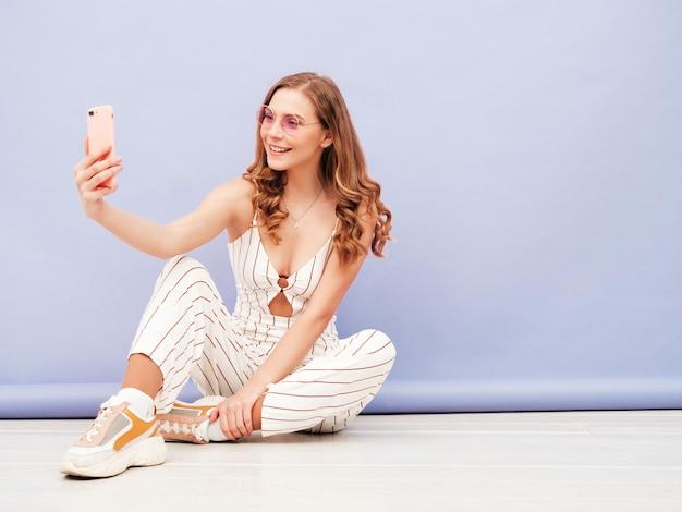 Giovane donna spensierata in posa vicino al muro viola in studio