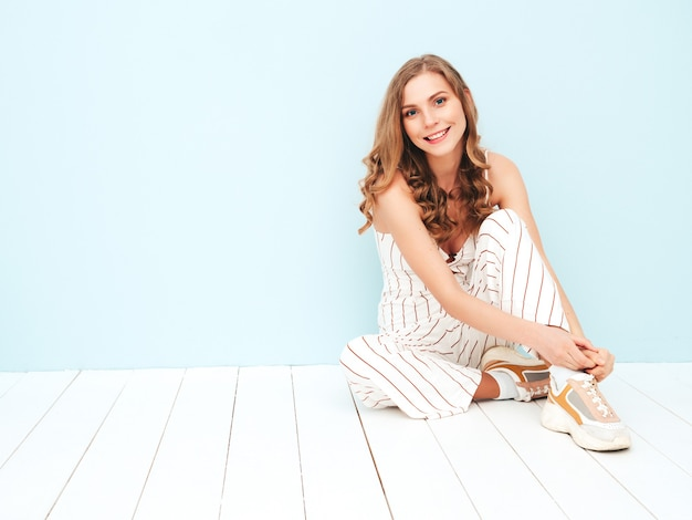 Giovane donna spensierata seduta vicino al muro azzurro in studio