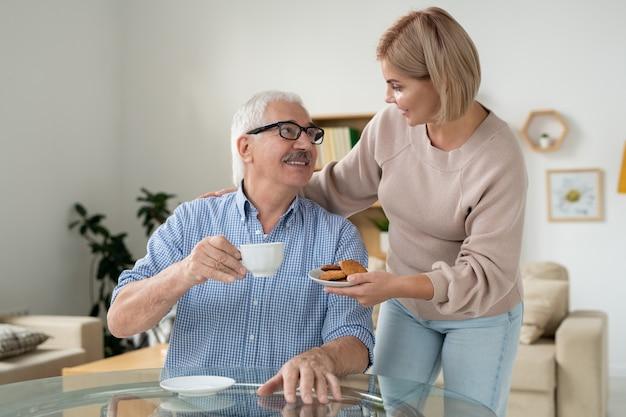Молодая заботливая дочь приносит печенье своему счастливому отцу-пенсионеру с чашкой чая, пока оба наслаждаются домашним отдыхом
