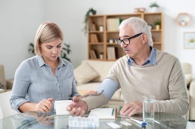 Молодая заботливая дочь заботится о своем больном отце на пенсии, используя тонометр для измерения его кровяного давления