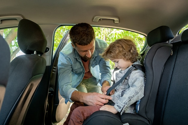 晴れた夏の週末にどこかに行く前に車の後部座席に座っている彼の幼い息子にシートベルトを着用する若い慎重な父親