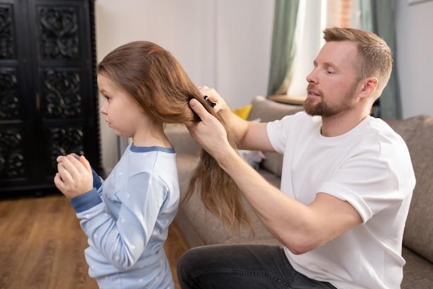 Молодой заботливый отец с расческой расчесывает длинные волосы своей милой маленькой дочери, сидя на диване перед ней в гостиной