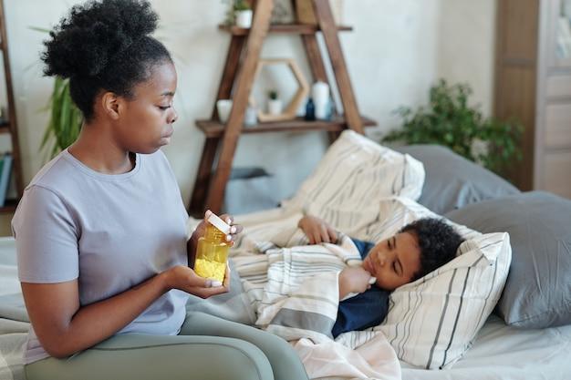 Молодая заботливая мать держит бутылку с таблетками, сидя на кровати возле своего больного маленького сына, лежащего под одеялом и собирающегося дать ему таблетку