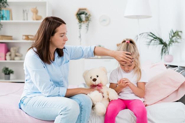 ソファに座って長いブロンドの髪と病気の小さな娘の額に触れる若い注意深い母親