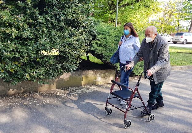 Молодой воспитатель сопровождает пожилого джентльмена, помогая ему гулять в парке