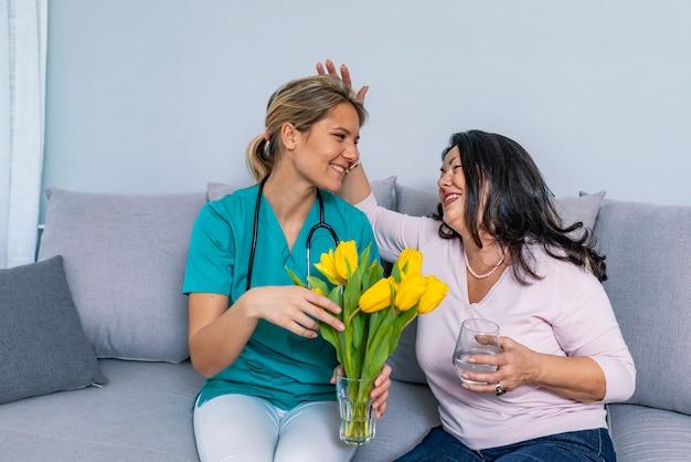 家庭訪問中に制服ハグ笑顔高齢女性の若い介護者