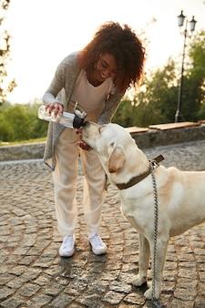 Молодая неосторожная леди дает воду своему питомцу в парке