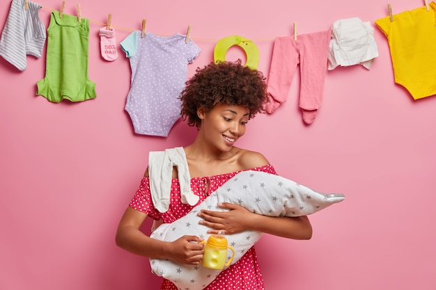 Young caring mother cares about newborn child, feeds with milk, enjoys happy moments of motherhood, poses at home. little baby on artificial feeding. babysitting, parenting concept. child birth