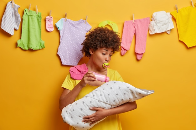 Young caring mother holds infant son wrapped in duvet on hands, feeds with milk from bottle, busy with motherhood, poses at home with washed baby clothes hanging in wall. family concept