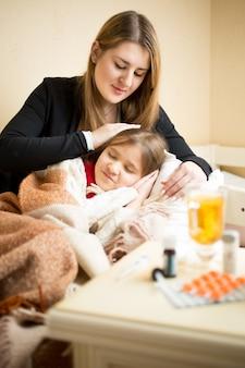 Молодая заботливая мать, лежа в постели с больной девушкой
