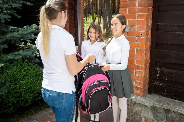 思いやりのある若い母親が娘を朝学校に見送ります