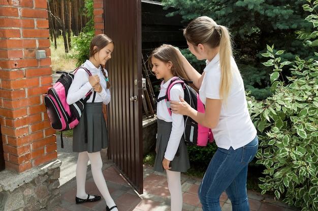 思いやりのある若い母親が娘たちを学校に見送ります