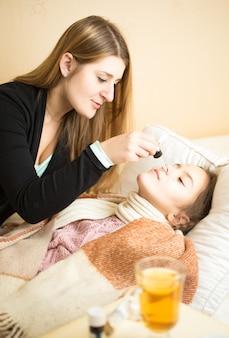 Молодая заботливая мать опрыскивает нос дочери, лежа в постели