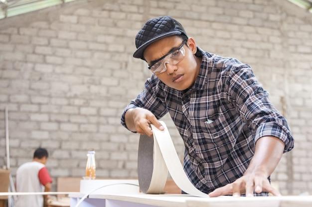 Молодой плотник наносит на мебель деревянный винил