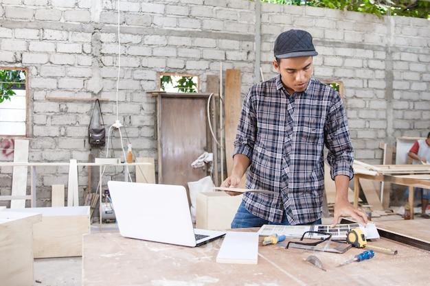 Молодой плотник проверяет образцы материалов с помощью интернета на ноутбуке
