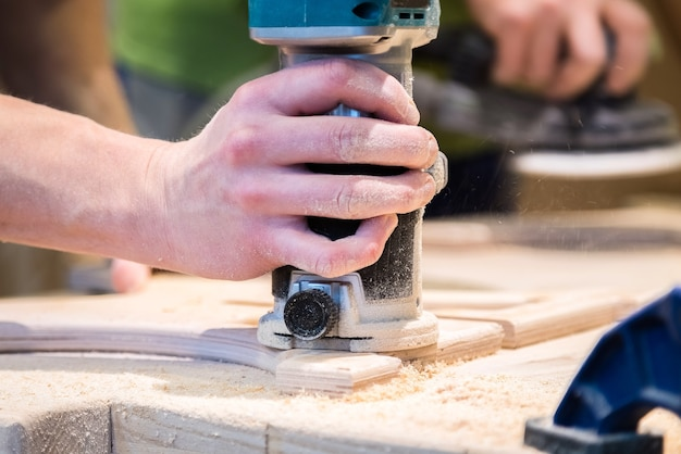 Young carpenter grinding cut out wood decoration with electric sandpaper machine