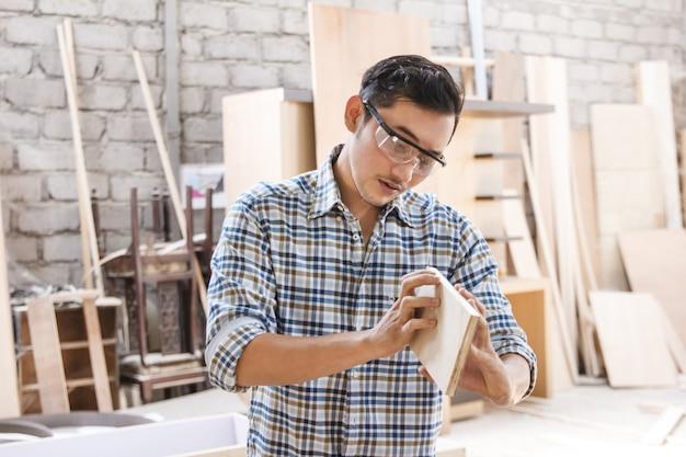 Молодой плотник контролирует качество своей продукции