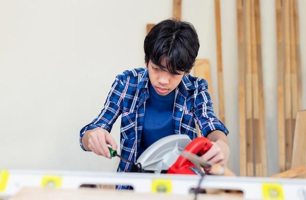 大工工房で丸鋸を固定するドライバーを使用する若い大工、職人工房で木工を学ぶ子供