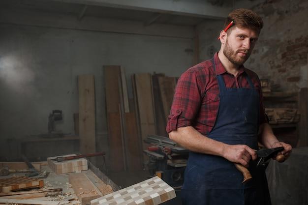 Молодой плотник с фартуком в своей мастерской