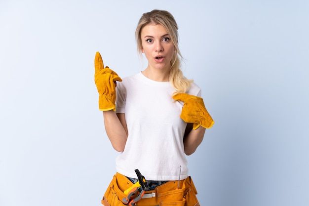 Young carpenter woman over isolated background