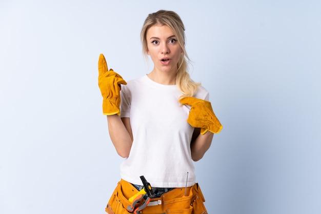 Молодая женщина плотника над изолированной предпосылкой