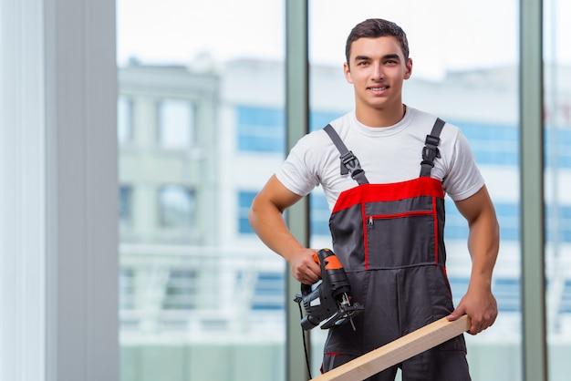 Молодой плотник работает на строительной площадке