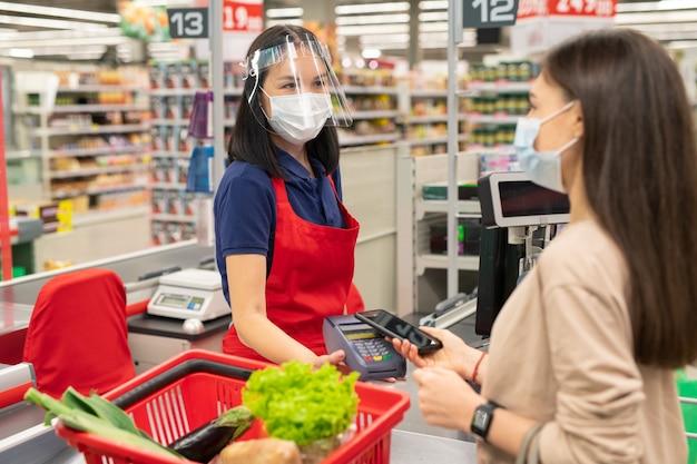 Молодой кассир в маске на лице проверяет продукты для покупателя в современном супермаркете