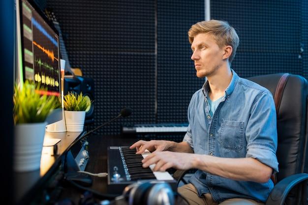 Молодой случайный блондин, глядя на экран компьютера, нажимая клавиши фортепианной клавиатуры в студии звукозаписи