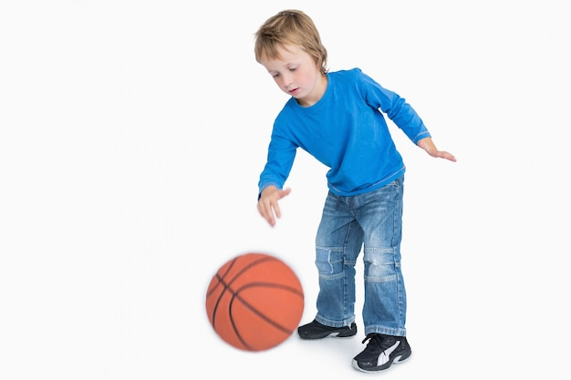 Young casual boy playing basketball