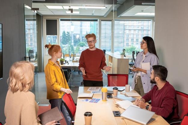Молодой случайный брокер стоит у стола и объясняет свою точку зрения или бизнес-стратегию коллегам на встрече стартапов в офисе