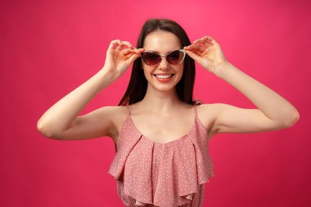 Молодая повседневная брюнетка женщина в солнцезащитных очках на розовом фоне