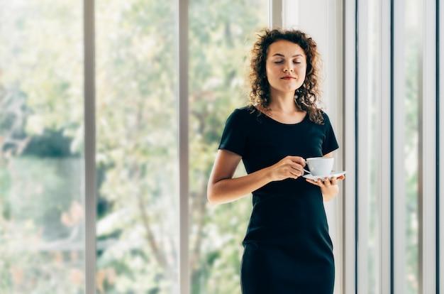 ホームオフィスの窓の横にあるコーヒーを飲みながらリラックスして目を閉じて笑顔で立っている若いカジュアルなビジネス女性