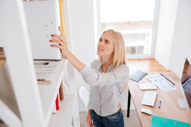 オフィスに立っている本棚からフォルダーを取る若いカジュアルなビジネス女性