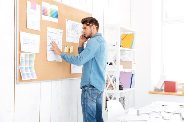 Young casual businessman looking at office task board and talking on the phone