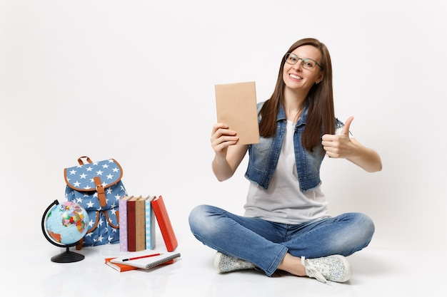 Young casual cheerful woman student in denim clothes holding book showing thumb up sitting near globe, backpack, school books